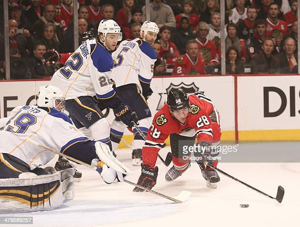 The Chicago Blackhawks' Ben Smith stretches to get to a puck in front of St Louis Blues goalie Ryan Miller left during the first period at the United...