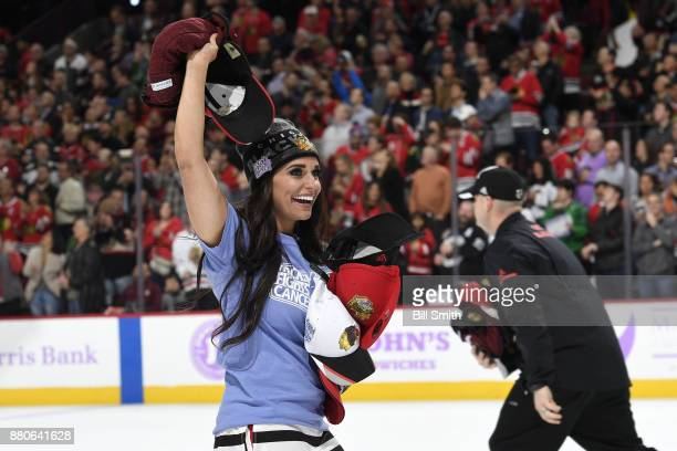 The Chicago Blackhawks icecrew pick up hats after Alex DeBrincat scored a hattrick in the second period against the Anaheim Ducks at the United...