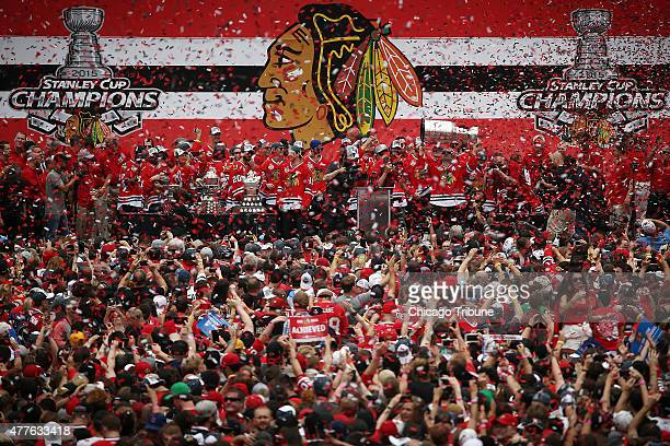 The Chicago Blackhawks' Patrick Sharp hoists the Stanley Cup trophy as confetti rains down on the crowd of fans during the championship celebration...