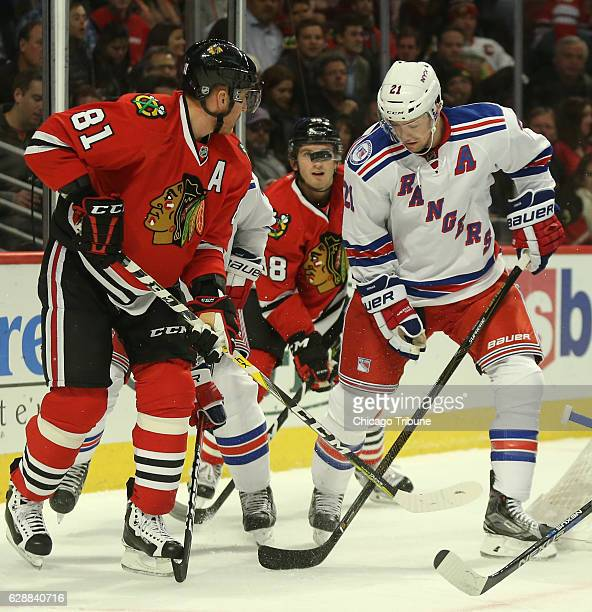 The Chicago Blackhawks' Ryan Hartman middle eyes the puck as teammate Marian Hossa and the New York Rangers' Derek Stepan skate by in the first...