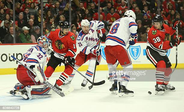 The Chicago Blackhawks' Ryan Hartman right tries to pass the puck against the New York Rangers defense in the first period at the United Center in...