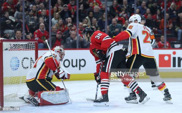 The Chicago Blackhawks' Ryan Hartman watches the puck shot by teammate Alex DeBrincat not pictured go past Calgary Flames netminder Mike Smith for a...