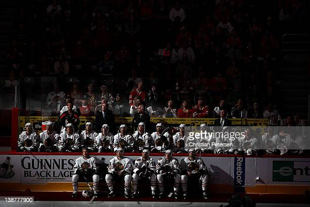 The Chicago Blackhawks sit on the bench and watch the pregame ceremony before the NHL game against the Phoenix Coyotes at Jobingcom Arena on February...