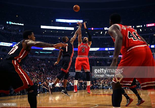 The Chicago Bulls' Carlos Boozer scores over the Miami Heat's Chris Bosh in the first quarter at United Center in Chicago Illinois on Wednesday March...