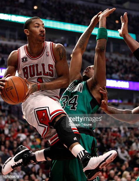 The Chicago Bulls' Derrick Rose drives against the Boston Celtics' Paul Pierce under the basket during the first quarter at the United Center in...