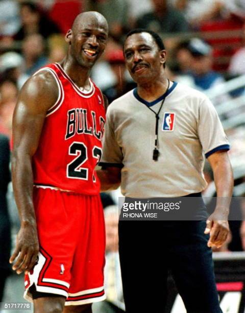 The Chicago Bulls guard Michael Jordon stands with referee Hugh Hollins as he watches teammate Ron Harper make a free throw with seconds remaining...