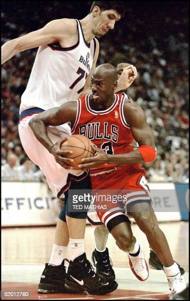 The Chicago Bulls' Michael Jordan tries to get around the Washington Bullets' Gheorghe Muresan in the fourth quarter in Landover, MD, 03 April....