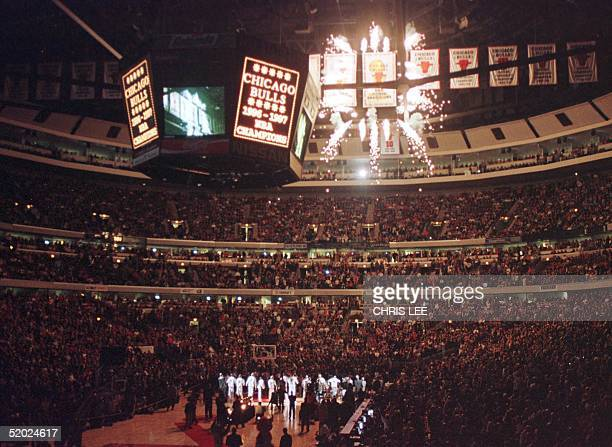 The Chicago Bulls team watches as the 1997 NBA Championship banner is revealed with a shower of fireworks prior to the 01 November game against the...