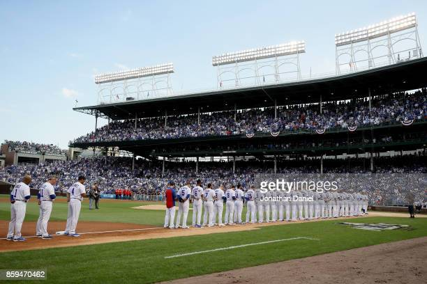 The Chicago Cubs and Washington Nationals stand for the singing of the national anthem before game three of the National League Division Series at...