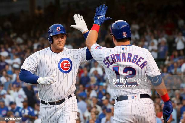 The Chicago Cubs' Anthony Rizzo highfives teammate Kyle Schwarber after Rizzo hit a solo home run during the first inning against the San Francisco...