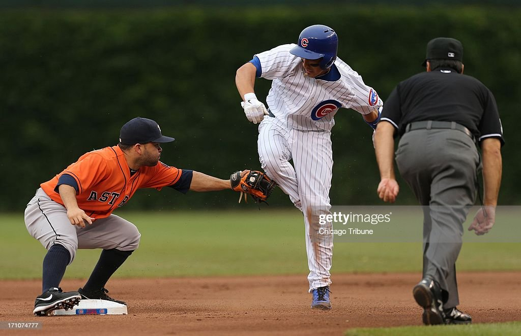 The Chicago Cubs' Darwin Barney is tagged out trying to steal second base by Houston Astros second baseman Jose Altuve, left, as umpire Phil Cuzzi, right, makes the call at Wrigley Field in Chicago, Illinois, on Friday, June 21, 2013.