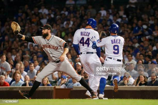 The Chicago Cubs' Javier Baez pushes teammate Anthony Rizzo out of the way before getting to first base safely past San Francisco Giants first...