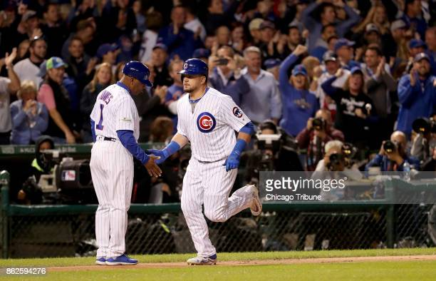The Chicago Cubs' Kyle Schwarber right heads to the plate after hitting a solo home run in the first inning against the Los Angeles Dodgers during...