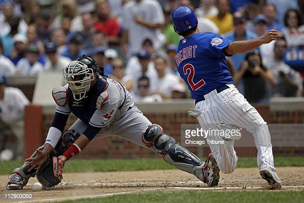 The Chicago Cubs' Ryan Theriot slides safely into home plate avoiding the tag Cleveland Indians catcher Victor Martinez in the fourth inning at...