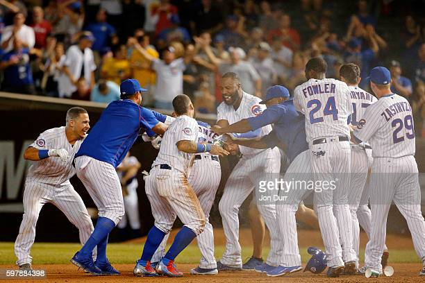 The Chicago Cubs try to rip off the jersey of Miguel Montero after he hit a walkoff RBI single against the Pittsburgh Pirates during the thirteenth...