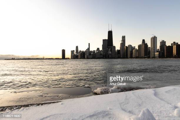 the chicago skyline with smoking chimneys during cold morning day with the lake michigan.. - waterfront stock pictures, royalty-free photos & images