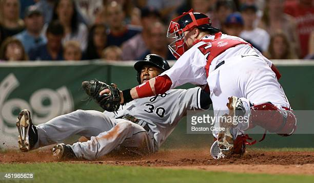 The Chicago White Sox Alejandro De Aza is tagged out by Boston Red Sox catcher Christian Vazquez as he tries to score on a seventh inning double by...