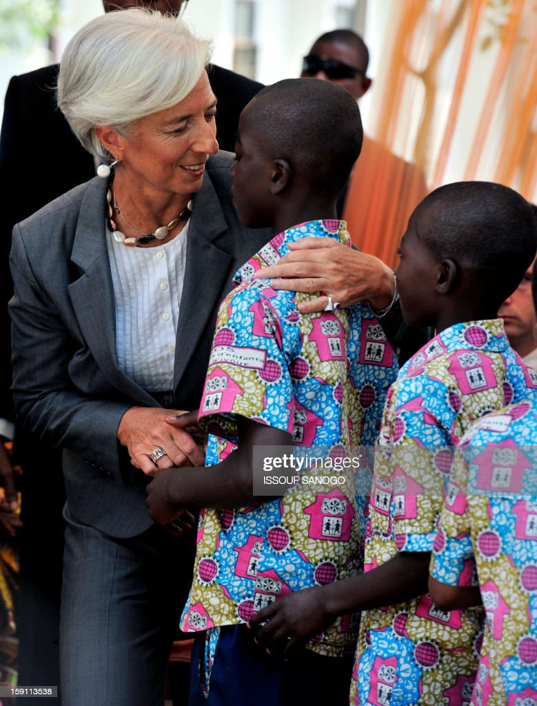 The chief of the International Monetary Fund, Christine Lagarde (L) embraces a boy as she visits an orphanage in Abobo, suburb of Abidjan on January 8, 2013. Lagarde, called for 'a second Ivorian economic miracle' during a visit to Abidjan as part of an African tour.