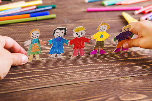 the child does figures of people of paper. Paper people on wooden background. Creative child play with craft. 854125684