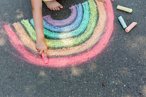 the child girl draws a rainbow with colored chalk on the asphalt. Child drawings paintings concept. Education and arts, be creative when back to school 1165196636