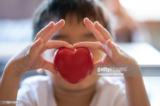 the child holding a red heart - medical symbol stock pictures, royalty-free photos & images