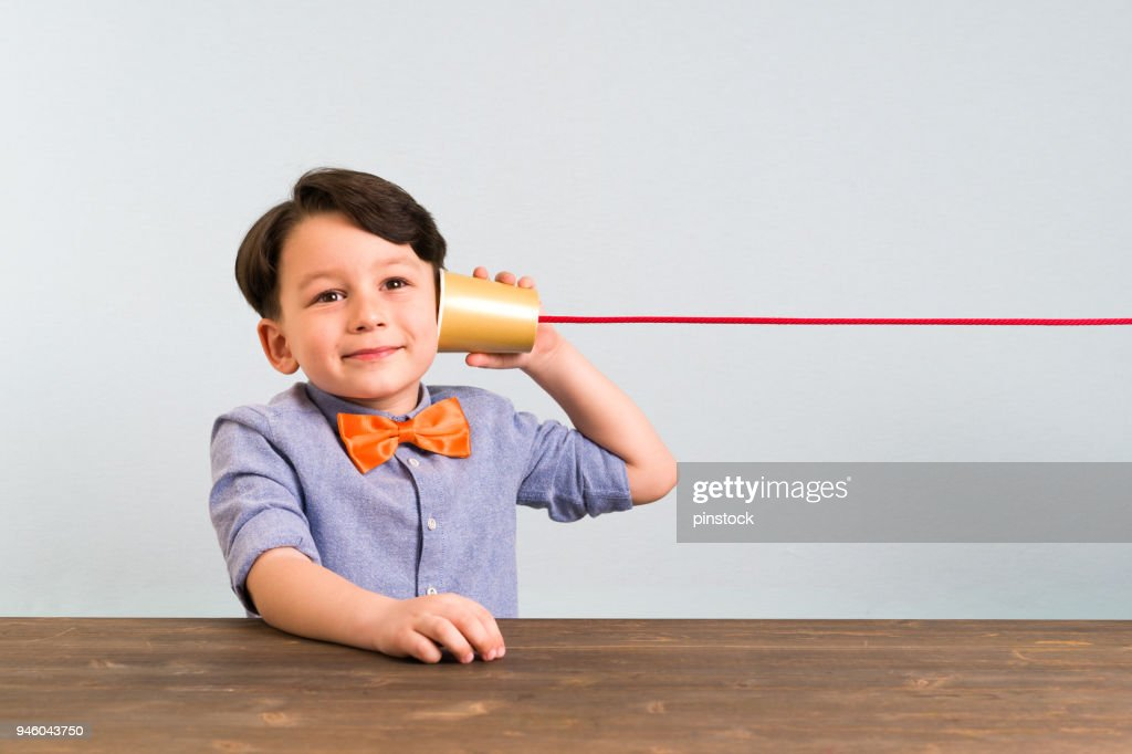 The child is using paper cup as a telephone : Stock Photo