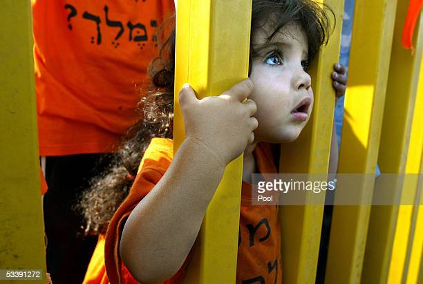 The child of a Jewish settler looks out of the entrance gate to the Jewish settlement of Gadid as settlers try to prevent security officers from...