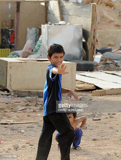 The child of a stateless family gestures outside his makeshift home in an impoverished neighbourhood east of the Saudi capital of Riyadh on July 10...