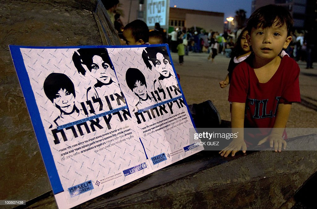 The child of immigrants plays next to placards against deportation during a protest calling on the Israeli government to allow illegal immigrants to stay in Israel, in Tel Aviv on May 25, 2010.