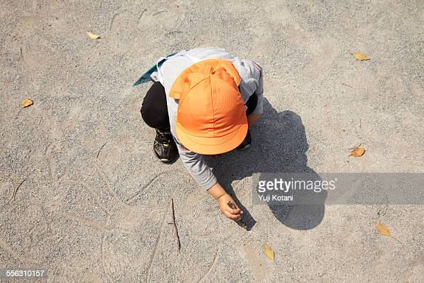 The child who draws a picture in the ground