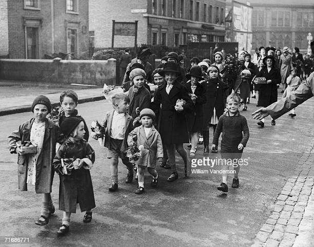 The children of Battersea carry their harvest festival gifts to St Peter's Church, 29th September 1935.