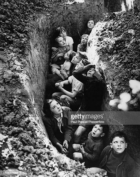The children of hoppickers take cover in a trench in Kent whilst watching a dogfight overhead during the Battle of Britain UK 1940 This image was...