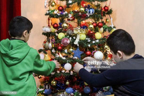The children of Iraqi Christian refugee Emile Saeed decorate a Christmas tree at a home in Jordan's capital Amman on December 13 where the family,...