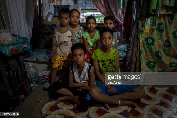 The children of Joel Mangalindan sits for a portrait inside their shanty house on June 30 2017 in Quezon city Philippines Joel Mangalindan was shot...