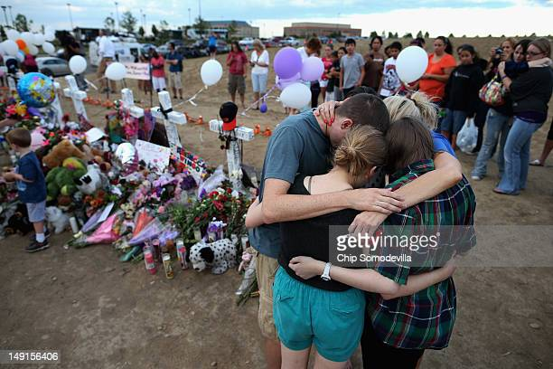 The children of movietheatershootingvictim Gordon Cowden embrace one another and pray at the makeshift memorial built across the street from the...