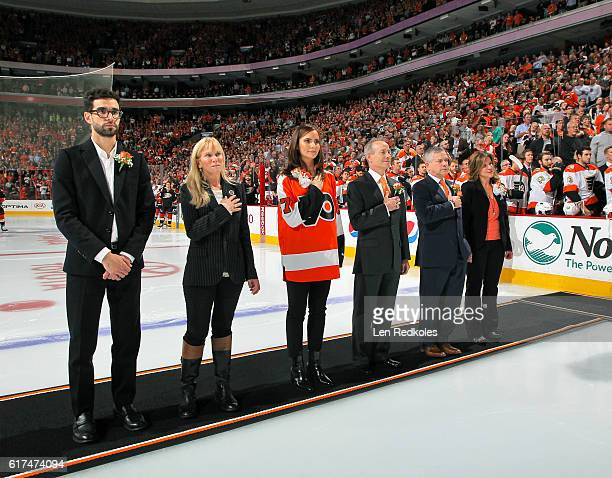 The children of the late owner Ed Snider Samuel Lindy Sarena Jay Craig and Tina stand on the ice during the pregame opening night ceremonies prior to...