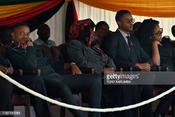The children of Zimbabwe's former President the late Robert Mugabe Robert Junior Chatunga and Bona sit in an official tribune at Rufaro stadium on...