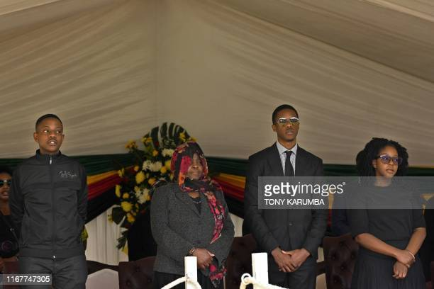 The children of Zimbabwe's former President the late Robert Mugabe Robert Junior Chatunga and Bona stand in an official tribune at Rufaro stadium on...