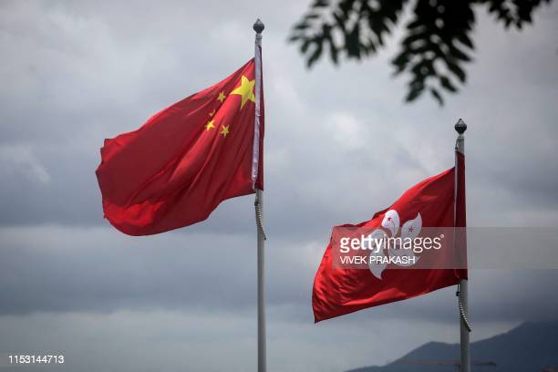 The China national flag is seen beside the Hong Kong flag in Hong Kong on July 2 a day after protesters broke into the government headquarters Hong...