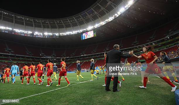 The China PR manager Bruno Bini welcomes his players onto the pitch prior to the Women's First Round Group E match between China PR and Sweden on Day...