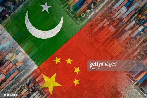 the chinese and pakistan flags imposed over shipping containers representing trade between the two countries. with a grainy, grunge edit. - pakistan stock-fotos und bilder