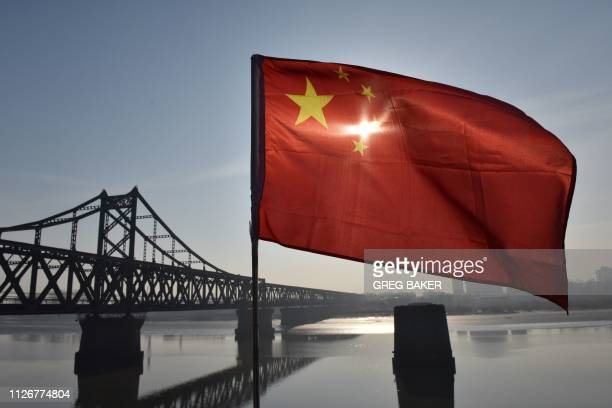The Chinese flag flies on the Yalu River Broken Bridge, with the Sino-Korean Friendship Bridge, and the North Korean city of Sinuiju behind, in the...