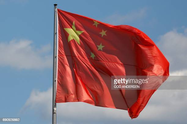 The Chinese flag flys prior to the arrival of Prime Minister Li Keqiang for talks at the Chancellery in Berlin on May 31 2017 / AFP PHOTO / Odd...