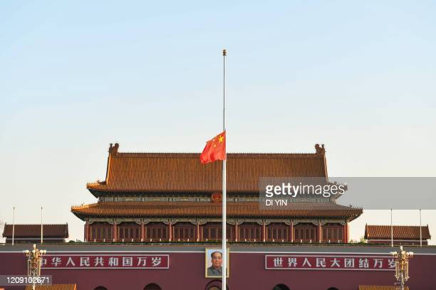The Chinese national flag flies at half-mast at the Tiananmen Square to mourn those who died in the fight against the novel coronavirus disease...