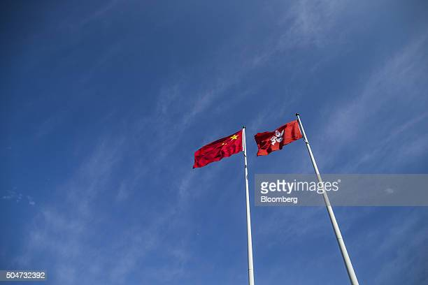 The Chinese national flag left and the Hong Kong flag fly outside the Legislative Council building in Hong Kong China on Wednesday Jan 13 2016 The...