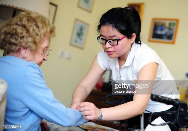 The Chinese nurse Song Xi helps Anna Wagner in a retirement home in Frankfurt/Main Germany 23 January 2014 The first five nursing staff from China...