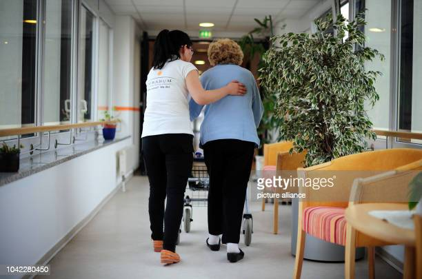 The Chinese nurse Song Xi walks with Anna Wagner in a retirement home in Frankfurt/Main Germany 23 January 2014 The first five nursing staff from...