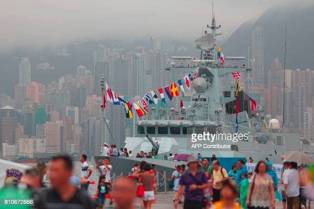 The Chinese People's Liberation Army Navy frigate Huizhou is seen past visitors at the Ngong Shuen Chau naval base on Stonecutters Island in Hong...
