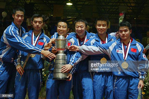 The Chinese team holds the trophy after winning the World Table Tennis Championship against Germany in Doha 07 March 2004 China's position as a table...