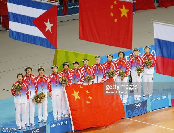 The Chinese team stand on the podium as the flags are raised after winning the gold medal in women's indoor volleyball during ceremonies on August 28...
